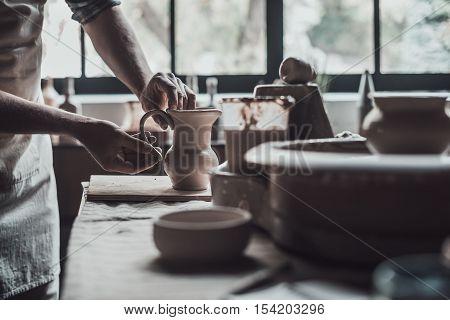 Potter at work. Close-up of potter making ceramic jug on at his workshop