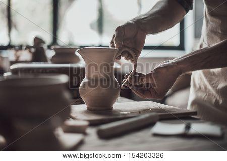 Potter making jug. Close-up of potter making ceramic jug on at his workshop