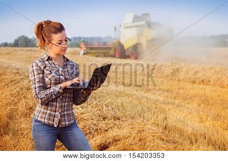 Young Pretty Farmer Girl In Glasses Make Notes On Notebook In Wheat Field While Combine Harvester Wo