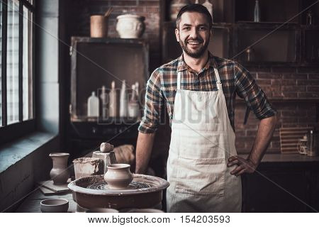 Cheerful potter. Confident young man looking at camera and smiling while standing in pottery