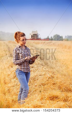Red-head Farmer Girl In Glasses Keeps A Crop Accounting On The Tablet In Wheat Field