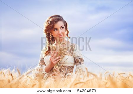 Pretty Woman Dressed In Embroidered Gown In Wheat Field