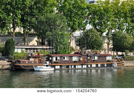 PARIS FRANCE - JULY 2: Floating house ship on the river Seine near the Swan Island in Paris.