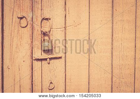Old rustic wooden door with metal lock and latch