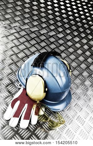 safety and protective work wear, hardhat, glases, earmuffs and gloves on a corrugated steel background