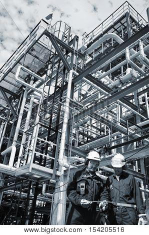 two oil and gas workers in front of large refinery pipelines construction inside refinery, selenium metal blue toning concept