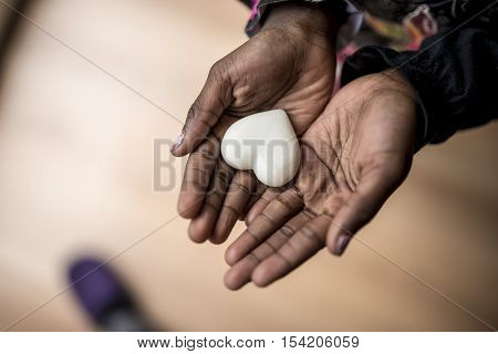 Top view of African-American girl hands holding a marble made heart shape.