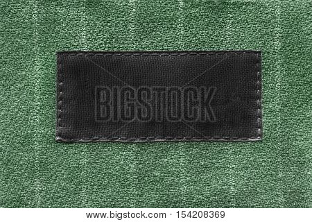 Blank black clothes label on green cloth as a background