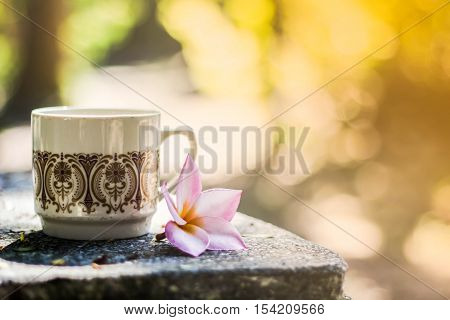 blurred background flower vase with cups coffee in coffee shop background and textures. blurred and soft focus on vintage color style.