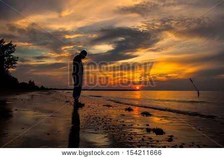 Silhouette of sad man in the beach during sunset in the background. Far away concept. Alone & lonely concept.