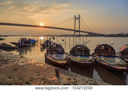 KOLKATA, INDIA - OCTOBER 29, 2016: Wooden country boats used for pleasure boat rides lined up at Princep Ghat on river Hooghly at sunset. The Vidyasagar Setu (bridge) at the backdrop.