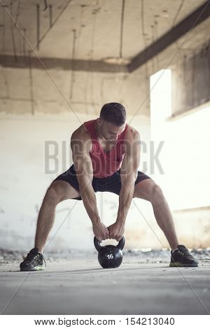 Sportsman working out in an abandoned building lifting a kettlebell weight