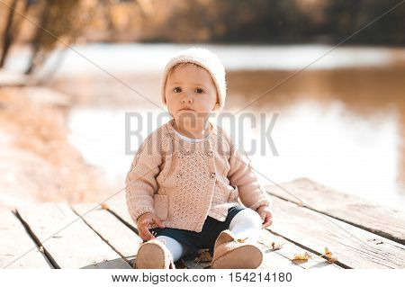 Cute baby girl 1-2 year old wearing stylish knitted clothes outdoors. Looking at camera. Autumn season.