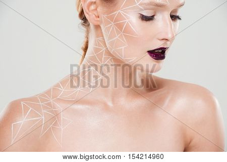 Cropped portrait of beauty woman with body art. looking down. Humble.