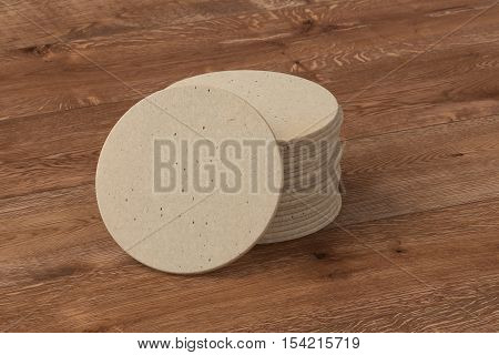Beer coaster. Isolated on wood bachround. Include clipping path. 3d render