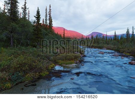 Evening mountain river landscape in arctic tundra.