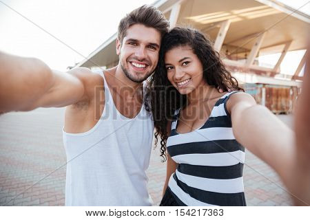 Smiling multiethnic young couple walking and making selfie outdoors