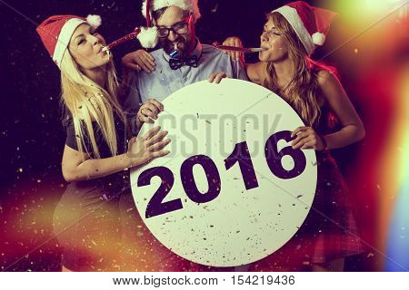 Three young people having fun at New Year's Eve Party blowing whistles and holding cardboard blank circle.