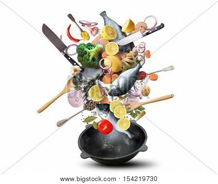 Large iron skillet with falling vegetables and fish