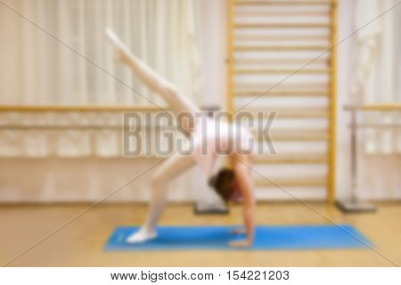 Young dancer ballerina performing gymnastic exercise while warming up at ballet class. blurry photo