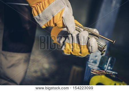 Choosing Right Screws. Construction Worker with Screws in Hands