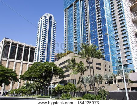 Tropical street with modern skyscrapers in Honolulu city (Hawaii).