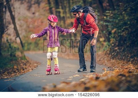 Roller Skate Family Learning. Father Teach His Daughter How to Roller Skating. Outdoor Caucasian Family Recreation