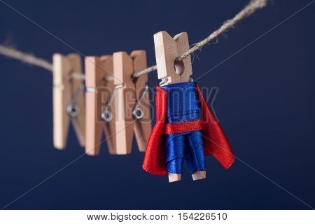 Powerful superstar clothespin peg character in blue suit red cape. leadership and wooden clothespins team at work. Dark blue background. soft focus. macro