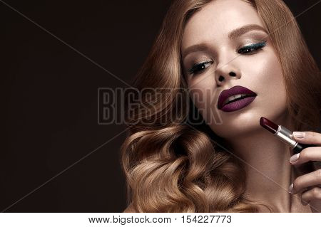 Beautiful blonde in a Hollywood manner with curls, dark lips, lipstick in hand. Beauty face and hair. Picture taken in the studio