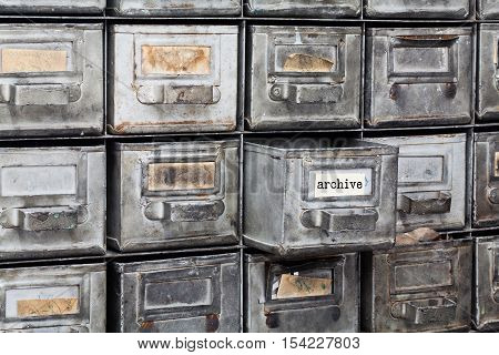 Archive old style interior. Closed metallic storage, filing cabinet. aged silver metal boxes with index cards.