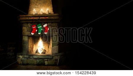 Romantic merry christmas postcard template. colorful stockings on fireplace collage. green red socks for gifts. Xmas interior with chimney place, candles. Copy space, copy-text black background photo