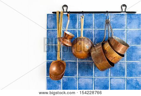 Kitchen interior with vintage copper utensils. old style cookware kitchenware set. Pots, coffee maker, kitchen spoon, skimmer hanging on blue tile wall. Copy space, white background photo