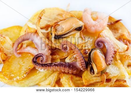 Octopus, mussel and shrimp with french fries. Seafood dish over fried potatoes. white background. copy space.