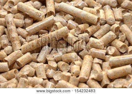 Wood pellets in the background. Biofuels. Cat litter.