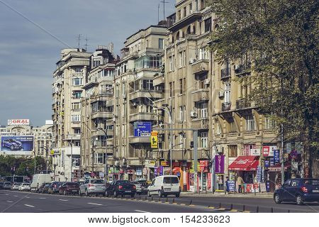 Bucharest Romania - April 22 2014: Urban scene with apartment blocks with kiosks groceries shops at ground floor in the old central residential district along the busy Corneliu Coposu boulevard.