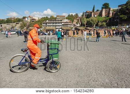 TBILISI, GEORGIA - OCT 16, 2016: City service worker in uniform cleans the street from garbage on a bicycle during Tbilisoba on October 16, 2016. Tbilisoba is traditional festival in Tbilisi, from 1979