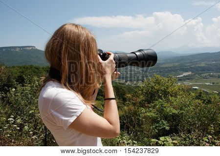 Young woman photographer taking landscape photo with professional camera with telephoto lens
