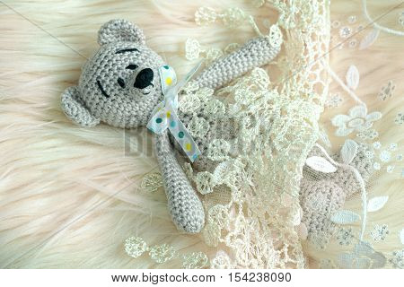 Handmade Teddy Bear With Ribbon Laying In Bed