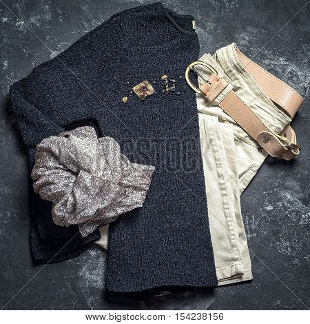 Flat Lay Top View Outfit Of Casual Woman. Black Sweater, Grey Scarf, Beige Jeans And Leather Belt On
