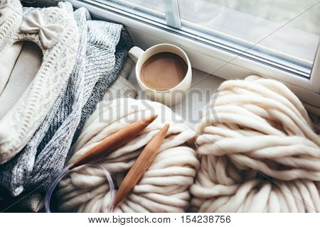 Stack of cozy knitted sweaters, thick yarn and wooden needles on window sill. Morning coffee in lazy winter weekend.