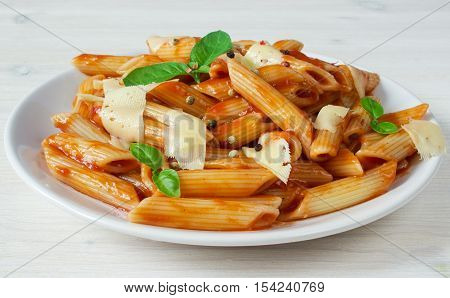penne pasta in tomato souce on light background