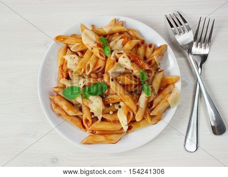 penne pasta in tomato souce on light background. view from above