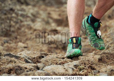 Cross country running feet run through rocky terrain