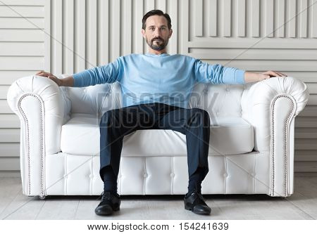 Like a boss. Optimistic delighted handsome man sitting on the white sofa and looking in front of him while having a break from work