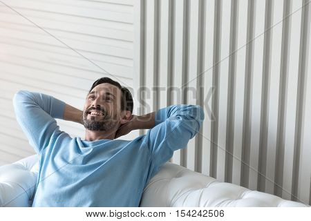 Feeling great. Nice cheerful bearded man holding his hands behind the head and smiling while being in a wonderful mood
