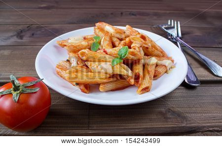 penne pasta in tomato souce on old wooden table
