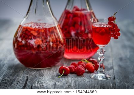 Liqueur made of wild berries on old wooden table