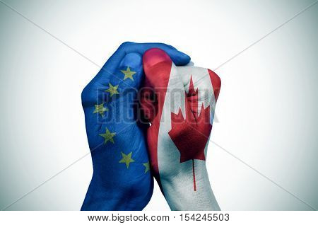 a hand patterned with the flag of the European Community envelops another hand patterned with the flag of Canada