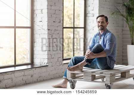 Absolutely happy. Positive cheerful good looking man sitting in the room and smiling while taking pleasure in his rest
