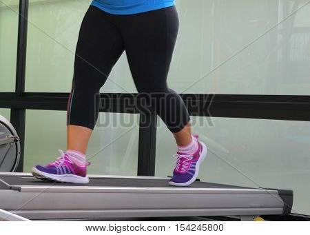 Jogging to lose weight to be healthylegs wearing sneakers running on treadmill.